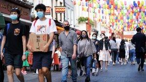 Ciudadanos con mascarilla caminan por el barrio chino de Londres, este domingo.