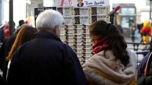 Varias personas adquieren décimos de Lotería de Navidad en los puestos instalados en la Puerta del Sol (Madrid).