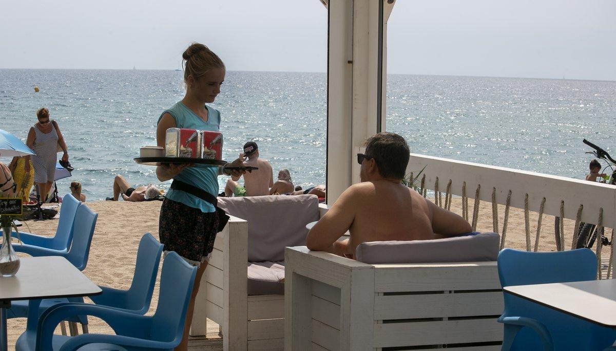 Una camarera en un chiringuito de playa trabajando durante el verano, en Badalona