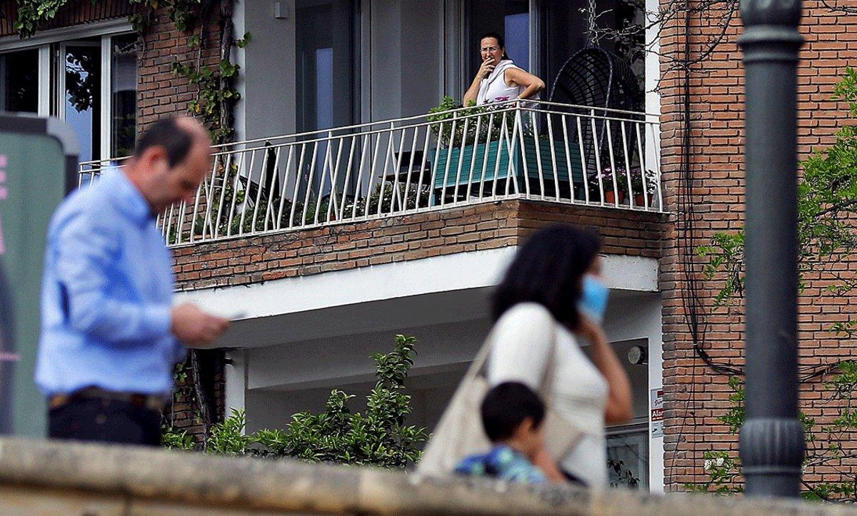 Una mujer observa desde el balcón de su casa a una pareja paseando con su hija, el domingo 26 de abril
