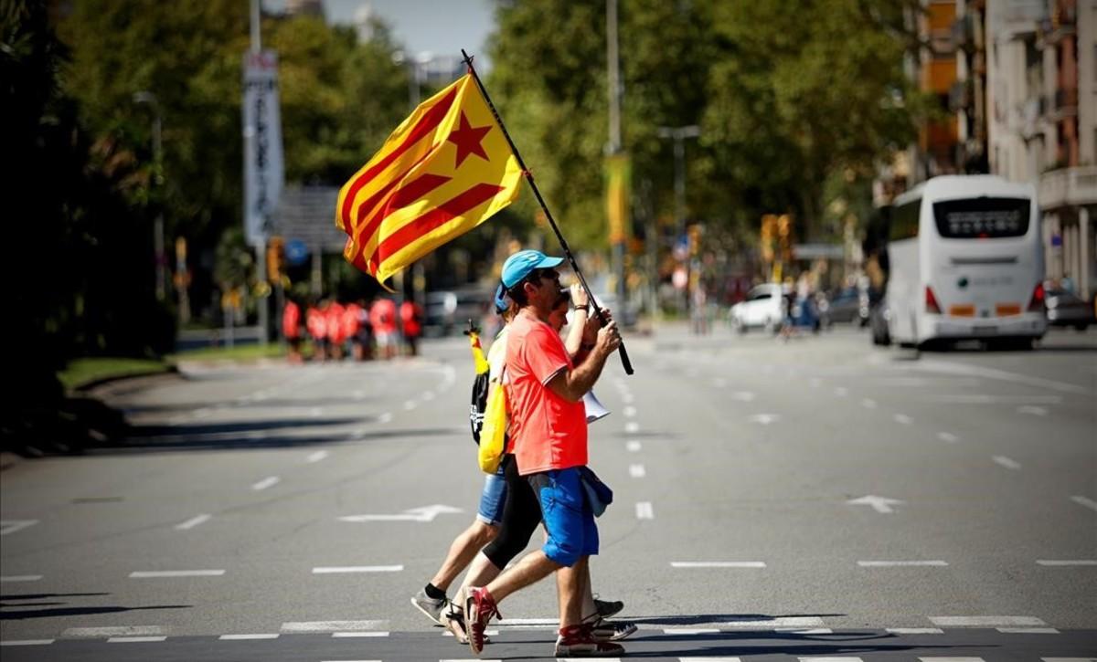 Dos ciudadanos con estelades cruzan una calle en Barcelona horas antes de la manifestación de la Diada.