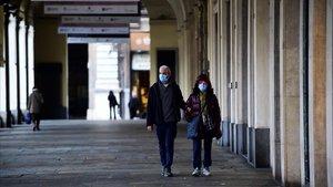 Dos personas con mascarilla caminan en una desierta plaza de San Carlo, este jueves en Turín.