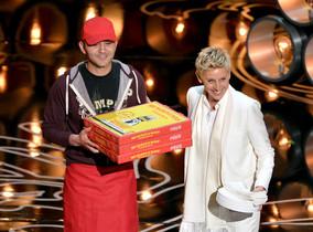 Ellen DeGeneres, junto al repartidor de pizzas, pregunta a los asistentes a la gala si tienen hambre.