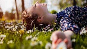 Una mujer, tendida en la hierba en primavera.