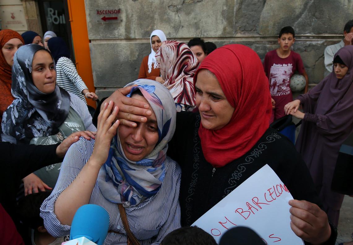 La hermana de Moussa y Driss Oukabir (izquierda) llora desconsolada en un acto contra el terrorismo, en Ripoll.