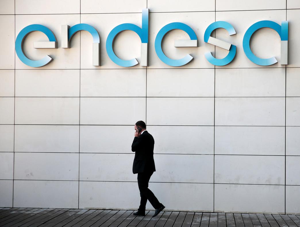 Un hombre camina bajo el logo de Endesa en la sede de la empresa en Madrid