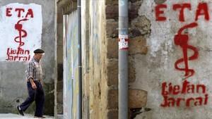 Un hombre pasa por delante de unas pintadas a favor de ETA, en Goizueta (Navarra).