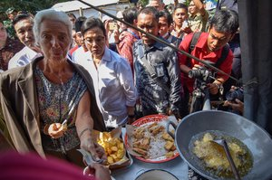 International Monetary Fund (IMF) Managing Director Christine Lagarde (L) buys traditional snacks from a vendor during her visit to an area affected by an earthquake at Gunungsari district, in West Lombok, Indonesia October 8, 2018. Antara Foto/Ahmad Subaidi via REUTERS ATTENTION EDITORS - THIS IMAGE WAS PROVIDED BY A THIRD PARTY. INDONESIA OUT. MANDATORY CREDIT: ANTARA FOTO