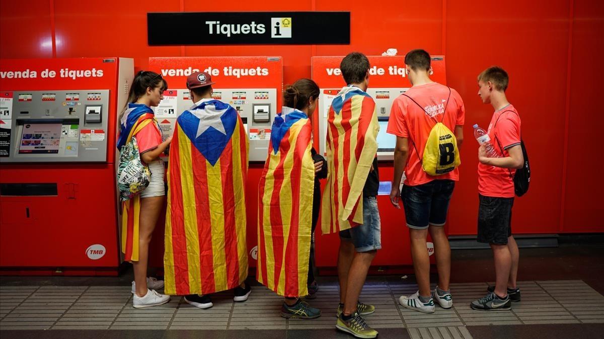 Jóvenes con banderas independentistas sacan el ticket del metro para ira la Diagonal.