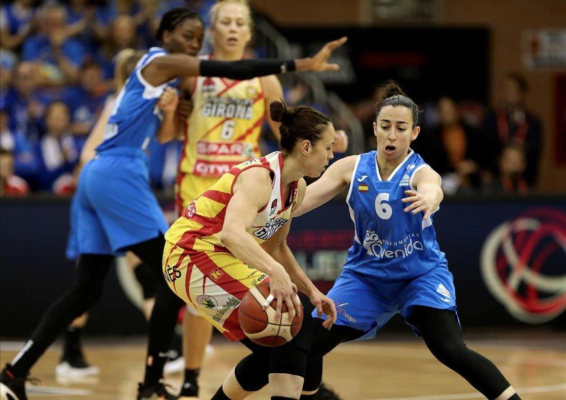La jugadora del Uni, Nuria Martínez, conduce el balón presionada por Silvia Domínguez