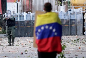 A man with a Venezuelan flag stands in front of riot security forces while rallying against Venezuela s President Nicolas Maduro s government in Caracas  Venezuela   REUTERS Ueslei Marcelino