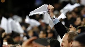 Los aficionados del Madrid exhiben su ira con pañuelos blancos tras el 0-4 del Barça.