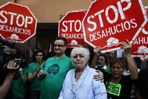 Maria Teresa Alsina i el seu fill, David Colmenero, envoltats per activistes del moviment contra els desnonaments, aquest matí a Badalona.