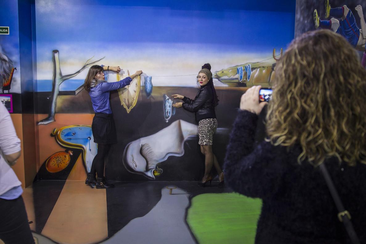 Unas visitantes se fotografían junto a una reproducción de 'La persistencia de la memoria', de Dalí.