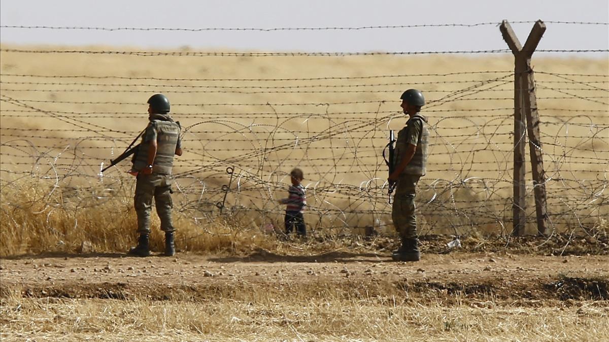 Un niño sirio espera tras las vallas de la frontera para cruzar hacia Turquía cerca de Akcacale (sureste), en el 2015.