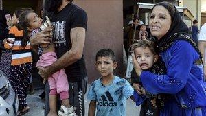 Vecinos de la localidad turca de Akcakale buscan refugio antelas explosiones de morteros lanzados desde Siria.