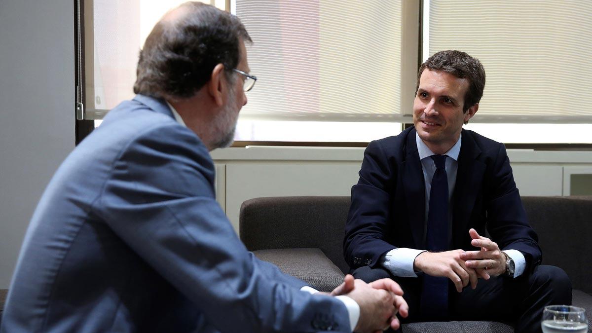 El nuevo presidente del Partido Popular, Pablo Casado, y el presidente del PP saliente, Mariano Rajoy, durante la reunión en la sede nacional del partido tras la celebración del Congreso Nacional Extraordinario del PP