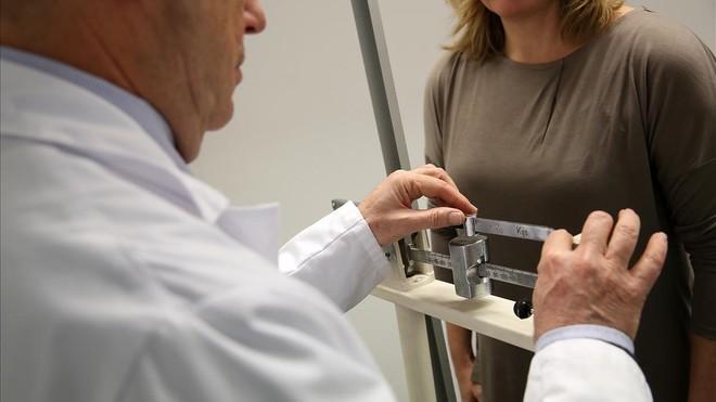 Un doctor pesa a una paciente en su consulta.