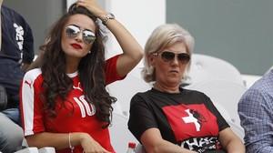 La madre de los hermanos Xhaka, con una camiseta dividida con los colores suizos y albaneses, junto a la pareja del suizo Granit.