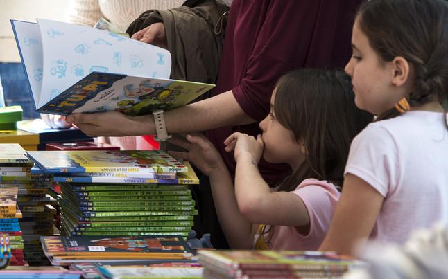 Una niña consulta varios libros en compañía de su padre, con motivo de la diada de Sant Jordi.
