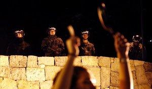 Soldados vigilan a manifestantes que golpean sartenes y cazuelas en una protesta frente a la residencia privada del presidente colombiano, Iván Duque, en Bogotá.