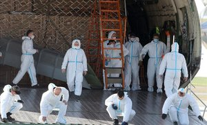 Trabajadores con trajes de protección descargan equipos sanitarios procedentes de China, en el aeropuerto de Paris-Vatry.