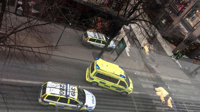 Una ambulància davant els cossos de les tres víctimes mortals en un atemptat amb camió a Estocolm.