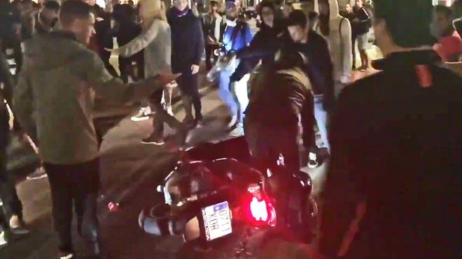 Unos manifestantes tiran a un motorista que no ha querido bajarse de la moto y pretendía continuar su paso, en el paseo de Gràcia con la calle València, este miércoles