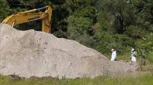 Varios peritos forenses desenterrando bolsas con partes de cuerpos humanos.