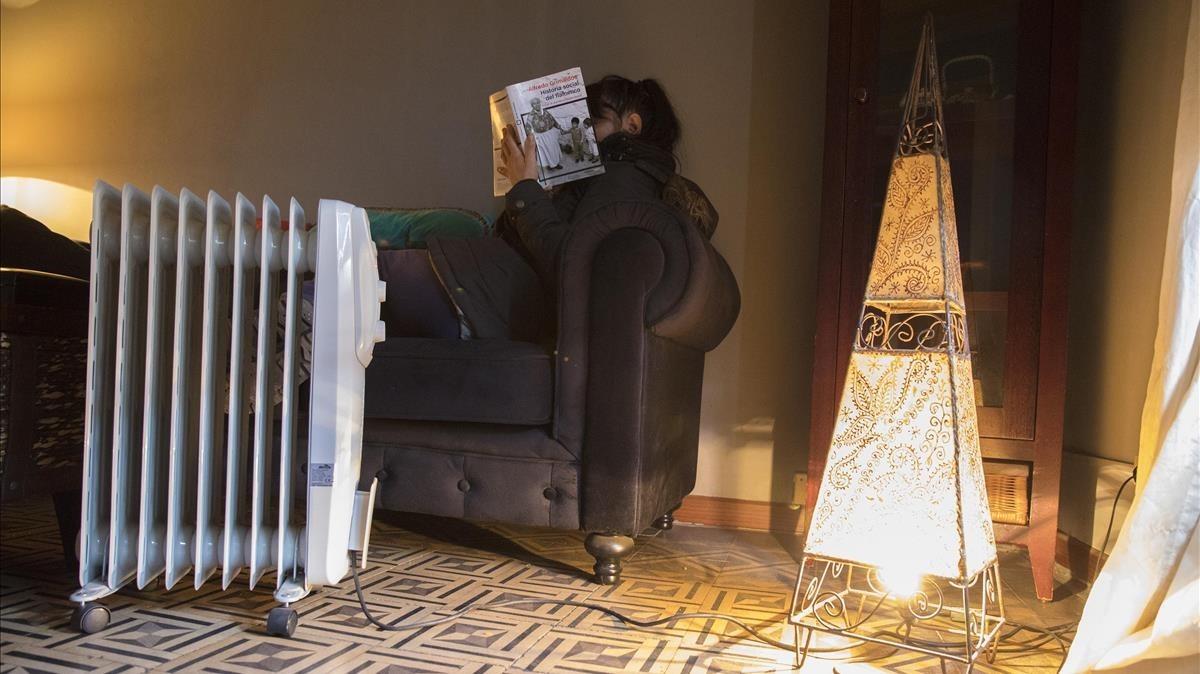 Una mujer se calienta en su casa con una estufa eléctrica durante la ola de frío en Barcelona.