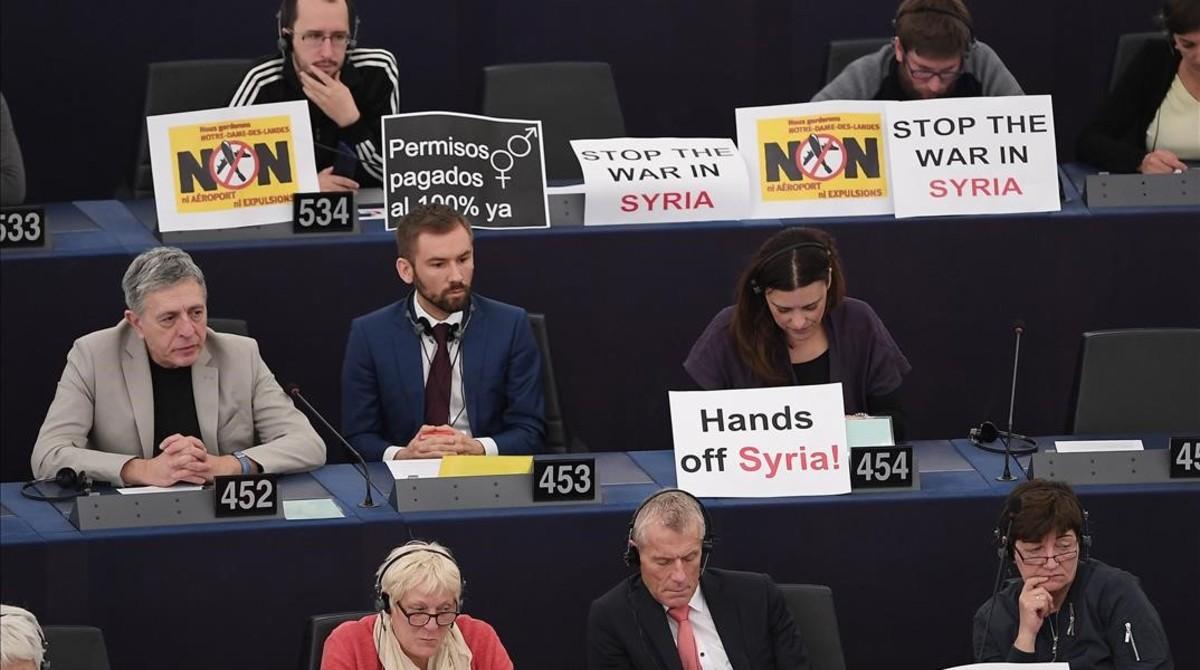 Europarlamentarios muestran carteles contrarios al ataque a las instalaciones del régimen de Asad.