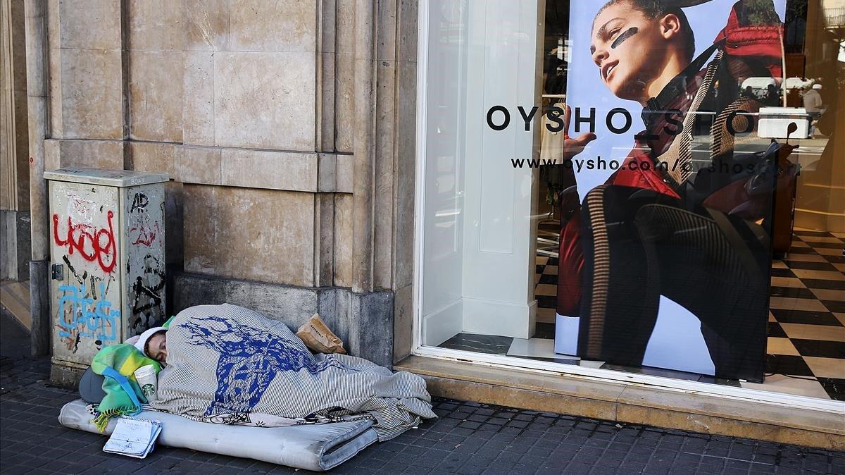 Una persona sin hogar, durmiendo en una calle del centro de Barcelona.