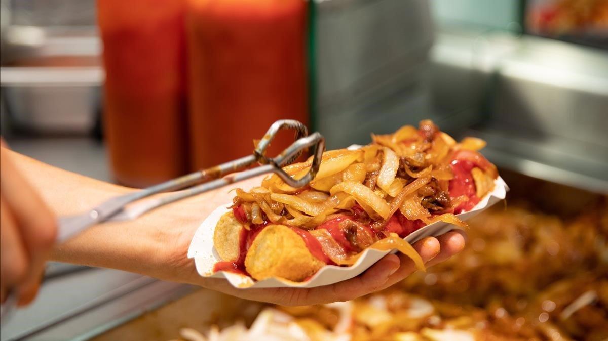 Un trabajador prepara una salchicha con patatas en un restaurante de comida rápida de Berlín