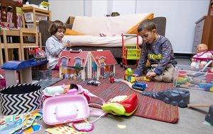 Júlia y Martí, de cinco años, con sus juguetes en el salón de su casa.