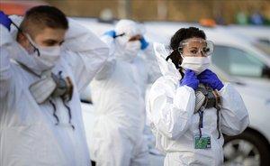 Tres trabajadores municipales se colocan los equipos de protección desechables antes de iniciar labores de desinfección en Bucarest (Rumania).