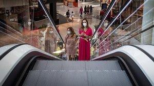 Una mujer en las escaleras mecánicas de Lagoh, uno de los centros comerciales de Sevilla que este lunes reabrieron sus puertas.