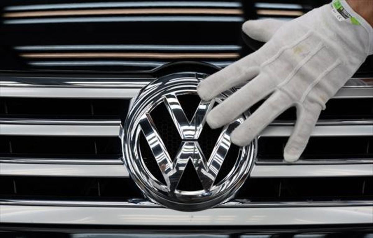 Marca 8Un empleado coloca el logotipo de Volkswagen a un vehículo.