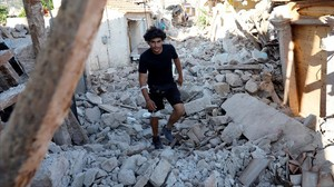 undefined38861604 a man walks among collapsed buildings at the village of vris170612203110