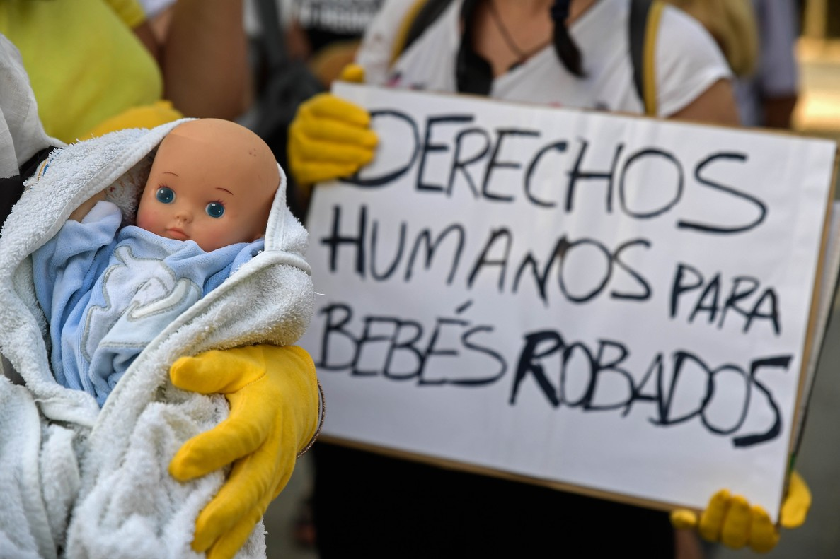 Demonstrators hold baby dolls and placards reading  Human rights for stolen babies  outside a provincial court in Madrid  on the first day of the first trial over thousands of suspected cases of babies stolen from their mothers during the Franco era  - A court in Madrid on September 4  2018  resumes the first trial for the theft of babies during the Franco dictatorship  1939-1975   in which Dr  Eduardo Vela  85  will appear in court facing the prosecution request of 11 years in prison.