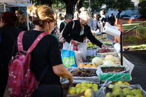 Una mujer compra frutas y verduras en una feria comunitaria para combatir la inflacion.