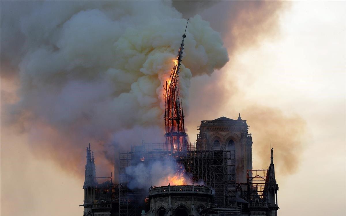 La agujade la histórica catedral de Notre-Dame se derrumba.
