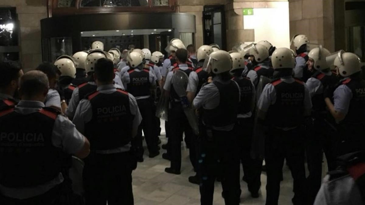 Agentes de Seguridad Ciudadana armados con cascos y desempeñando funciones de orden público, dentro de un Parlament asediado por manifestantes.