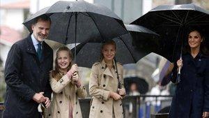 El rey Felipe VI, la princesa Leonor, la infanta Sofía y la reina Letizia, bajo la lluvia, en su visita a Asiegu (Asturias).