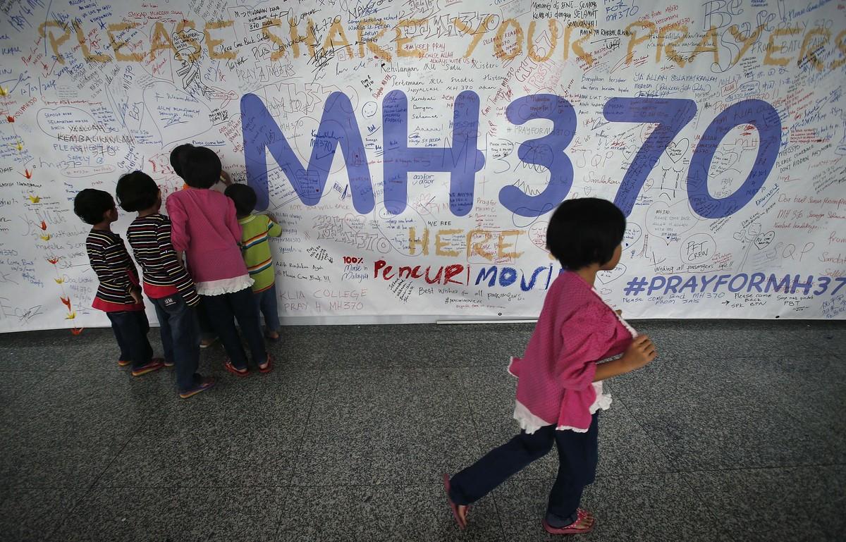 Un grupo de niños escribiendo mensajes esperanzadores para los familiares de las personas que desaparecieron en el vuelo MH370, de la compañía Malasya Airlines, en mayo del2014.