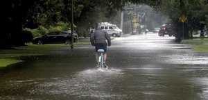 Un hombre circula con una bicicleta por una calle anegada en Beaumont (Tejas).