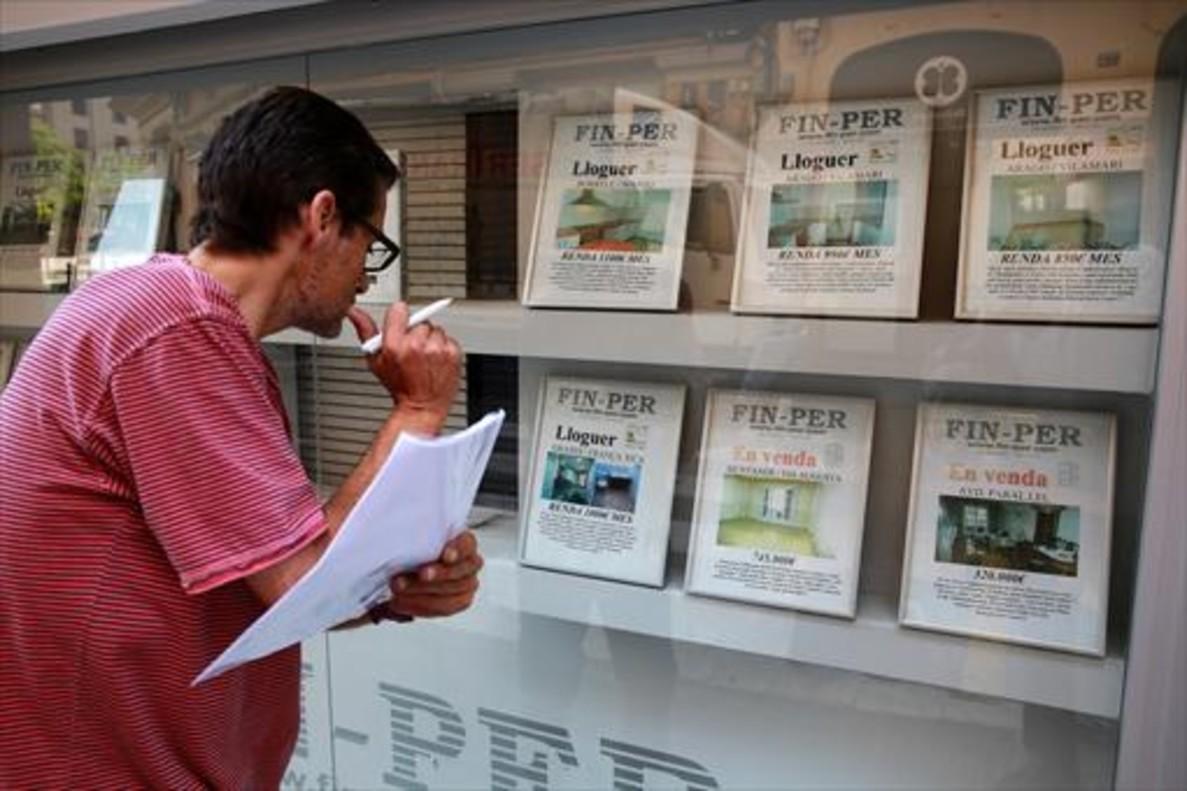 Un hombre mira una agencia de la calle de Elkano del Poble Sec.