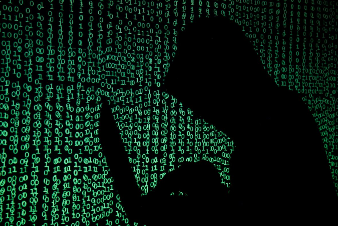 A hooded man holds a laptop computer as cyber code is projected on him in this illustration picture taken on May 13 2017 Capitalizing on spying tools believed to have been developed by the U S National Security Agency hackers staged a cyber assault with a self-spreading malware that has infected tens of thousands of computers in nearly 100 countries REUTERS Kacper Pempel Illustration