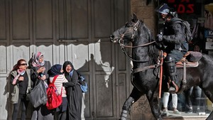 Mujeres palestinas reaccionan con temor ante el paso de un soldado israelí a caballo.