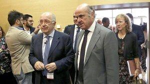 El excomisario europeo Joaquín Almunia junto al vicepresidente del Banco Central Europeo, Luis de Guindos, y delante de la subgobernadora del Banco de España, Margarita Delgado, en el X aniversario del FROB.