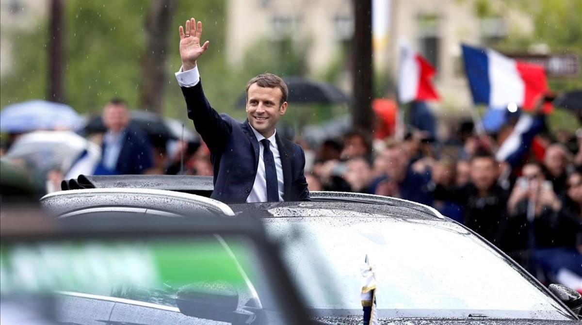 Macron saluda a la multitud desde su coche presidencial en París.